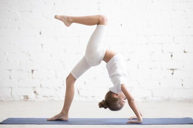 girl-child-one-legged-wheel-pose-white-studio-background_1163-2793