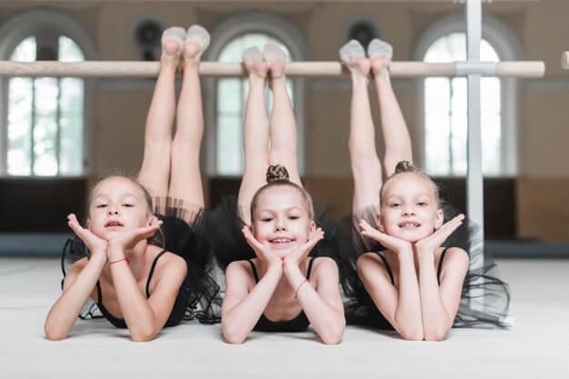 portrait-three-ballerina-girls-poising-front-barre_23-2147856612